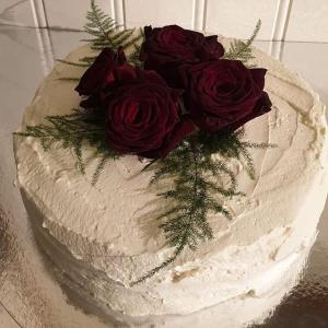 Bröllopstårta uppstruken med grädde, dekorerad med levande rosor
