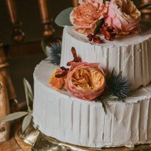 Bröllopstårta uppstruken med smörkräm, dekorerad med levande blommor